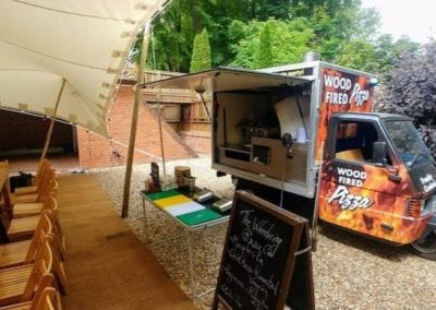 Piaggio Truck set up to serve pizza at an event on a sunny day